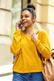 Жизнерадостная женщина идя outdoors и говоря на мобильном телефоне Стоковая Фотография