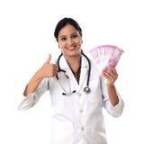 Жизнерадостная женщина доктора держа индейца 2000 примечаний рупии с большим пальцем руки вверх показывать Стоковое Изображение RF