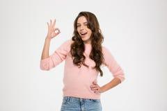 Жизнерадостная женщина подмигивая и показывая одобренному знаку Стоковые Фотографии RF