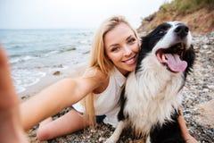 Жизнерадостная женщина принимая selfie с собакой на пляже стоковое фото