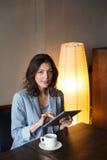 Жизнерадостная женщина сидя внутри помещения используя планшет Стоковые Изображения RF