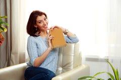 Жизнерадостная женщина сидя на софе и держа книгу Стоковые Фото