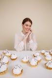 Жизнерадостная женщина сидя на таблице с пирожными и усмехаться Стоковые Фото