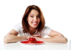 Жизнерадостная женщина сидя на таблице с свежим тортом клубники стоковое изображение