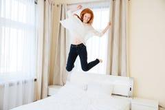 Жизнерадостная женщина скача на кровать стоковые изображения