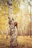 Жизнерадостная женщина смотрит вне от за дерева стоковые фотографии rf