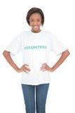Жизнерадостная женщина с руками на бедрах нося добровольную футболку стоковые изображения