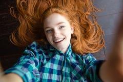Жизнерадостная женщина redhead делая изображение собственной личности лежа на поле Стоковое фото RF