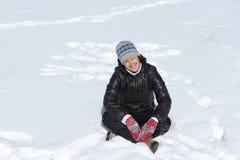 Жизнерадостная женщина squating положив ногу на ногу на снеге Стоковые Фотографии RF