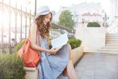 Жизнерадостная книга усаживания и чтения молодой женщины в городе Стоковое Изображение