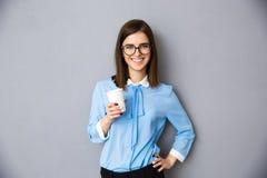 Жизнерадостная коммерсантка держа чашку с кофе Стоковая Фотография