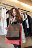 Жизнерадостная курчавая молодая дама в магазине одежды с хозяйственными сумками Стоковые Изображения RF