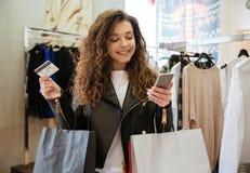 Жизнерадостная курчавая молодая дама держа кредитную карточку и телефон Стоковое Изображение