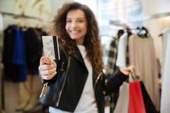 Жизнерадостная курчавая молодая дама с хозяйственными сумками Фокус на карточке Стоковая Фотография