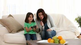 Жизнерадостная мама ободряя ее дочь сыграть видеоигры видеоматериал