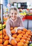 Жизнерадостная маленькая девочка покупая сладостные мандарины Стоковые Изображения RF