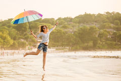 Жизнерадостная маленькая девочка при зонтик радуги имея Стоковое фото RF