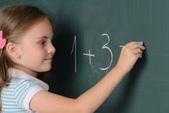 Жизнерадостная маленькая школьница писать o стоковая фотография rf