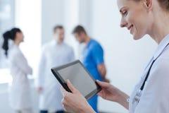 Жизнерадостная медсестра используя цифровой прибор в клинике Стоковое фото RF