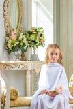 Жизнерадостная милая девушка сидя с подняла Стоковое Изображение