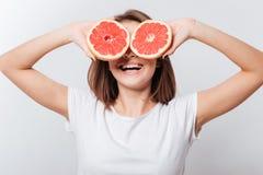 Жизнерадостная молодая дама держа грейпфрут Стоковые Изображения