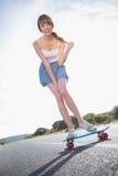 Жизнерадостная молодая женщина балансируя на ее скейтборде стоковые фотографии rf