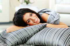 Жизнерадостная молодая женщина лежа на поле с подушками Стоковое Изображение