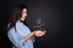 Жизнерадостная молодая женщина держа цветок Стоковое Изображение