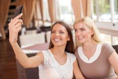 Жизнерадостная молодая женщина делает selfie в кафе Стоковые Фотографии RF