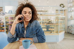 Жизнерадостная молодая женщина используя телефон в кафе Стоковое Фото