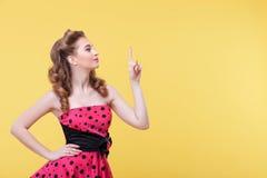 Жизнерадостная молодая женщина показывает что-то с утехой Стоковое Изображение