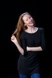 Жизнерадостная молодая женщина показывая ей волосы и смеяться над Стоковая Фотография