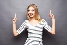 Жизнерадостная молодая женщина показывая copyspace, визуальное мнимое или некоторое стоковое фото