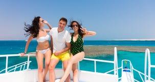 Жизнерадостная молодость смеясь над и стоя на яхте на солнечной сумме Стоковая Фотография RF