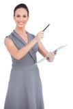 Жизнерадостная обольстительная модель указывая с ручкой стоковое изображение