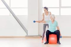 Жизнерадостная пожилая женщина сидя на шарике фитнеса Стоковое Фото