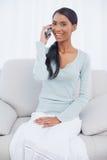Жизнерадостная привлекательная женщина сидя на уютной софе имея телефонный звонок стоковые изображения rf