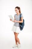 Жизнерадостная привлекательная женщина с рюкзаком используя планшет стоковые изображения