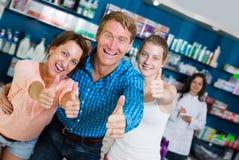 Жизнерадостная семья из трех человек держа большие пальцы руки вверх Стоковые Изображения RF