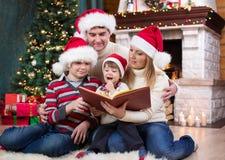 Жизнерадостная семья из четырех человек читая совместно дальше Стоковое фото RF