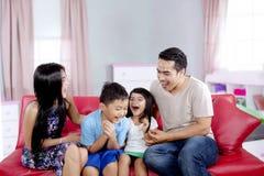 Жизнерадостная семья имея потеху на софе Стоковое Изображение RF