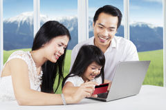 Жизнерадостная семья наслаждаясь ходить по магазинам онлайн Стоковое Фото
