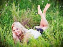 Жизнерадостная симпатичная молодая женщина лежа среди зеленой травы и цветков Стоковые Изображения RF
