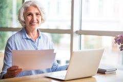 Жизнерадостная старшая женщина сидя на таблице стоковое фото