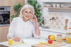 Жизнерадостная старшая домохозяйка высчитывая отечественные расходы стоковая фотография rf