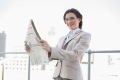 Жизнерадостная стильная коричневая с волосами коммерсантка читая газету Стоковое фото RF