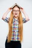Жизнерадостная студентка держа книги на голове Стоковая Фотография
