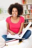 Жизнерадостная студентка сидя на софе стоковая фотография rf