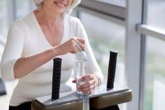Жизнерадостная тонкая старшая женщина имея воду после разминки спортзала стоковая фотография rf