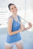 Жизнерадостная худенькая женщина в sportswear держа измеряя ленту стоковое фото rf